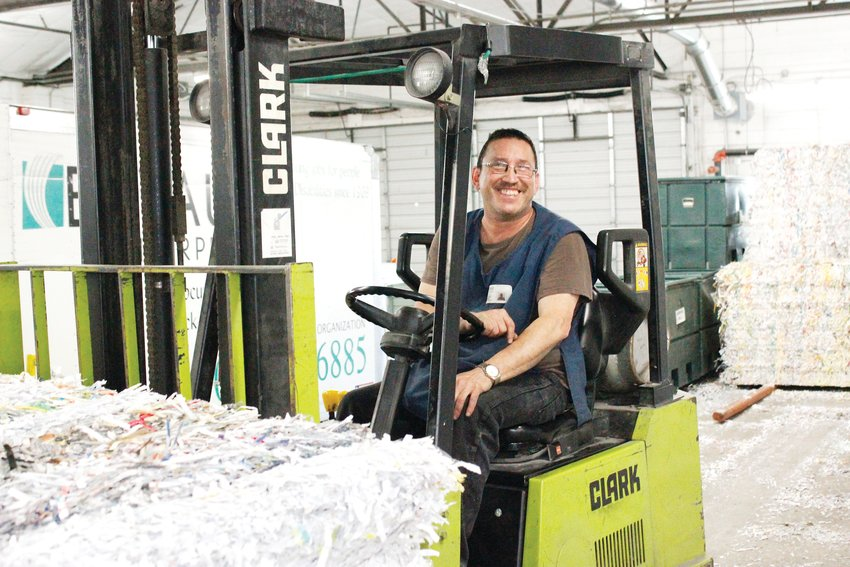 Joe Tinao operates a forklift in the paper shredding room at Bayaud Enterprises. The shredding business is one of the many avenues that the nonprofit uses to connect people to jobs.
