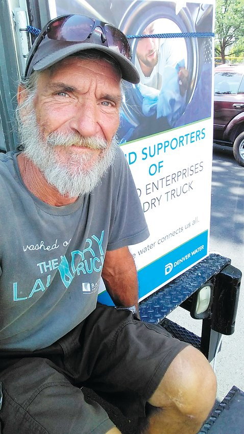 Ray Laell sits on the back of the Bayaud Enterprises Laundry Truck. In additon to helping connect people struggling with mental illness and homelessness to jobs, the nonprofit offers several mobile services, including its two laundry trucks and a new shower truck.