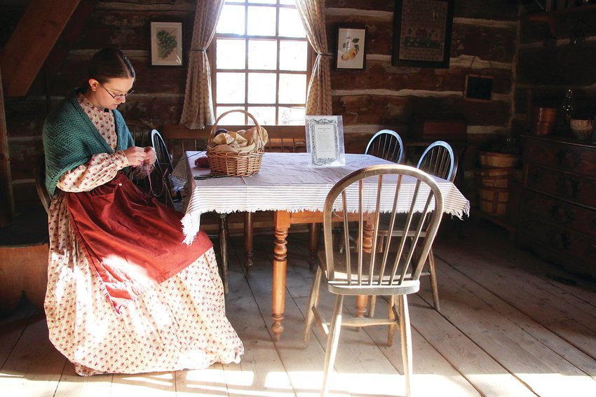 Historical interpreter Mary Hathaway knits a hat in the Littleton Museum's 1860s cabin.