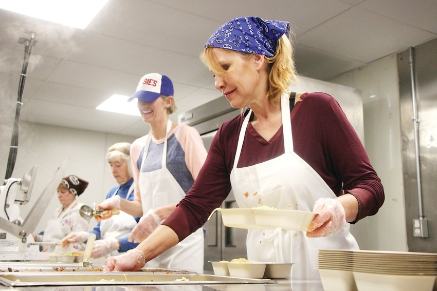 Kelly Eisen and fellow Meals on Wheels volunteers prepare a spaghetti lunch on Jan. 6. TLC Meals on Wheels, which provides healthy food and companionship for homebound seniors and others, is up and running in their new home at Broadway and Arapahoe Road.