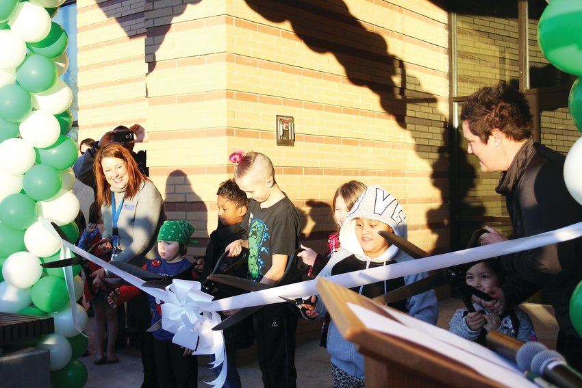 Englewood Superintendent Wendy Rubin, left, Eli McBridge, Malik Diouf, Nathan Owens, Xandria Lindsey, Maria Infante Torres, Marialuisa Monge and Bishop Elementary Principal Shanna Martin cut the ribbon to officially open the new Bishop Elementary building.