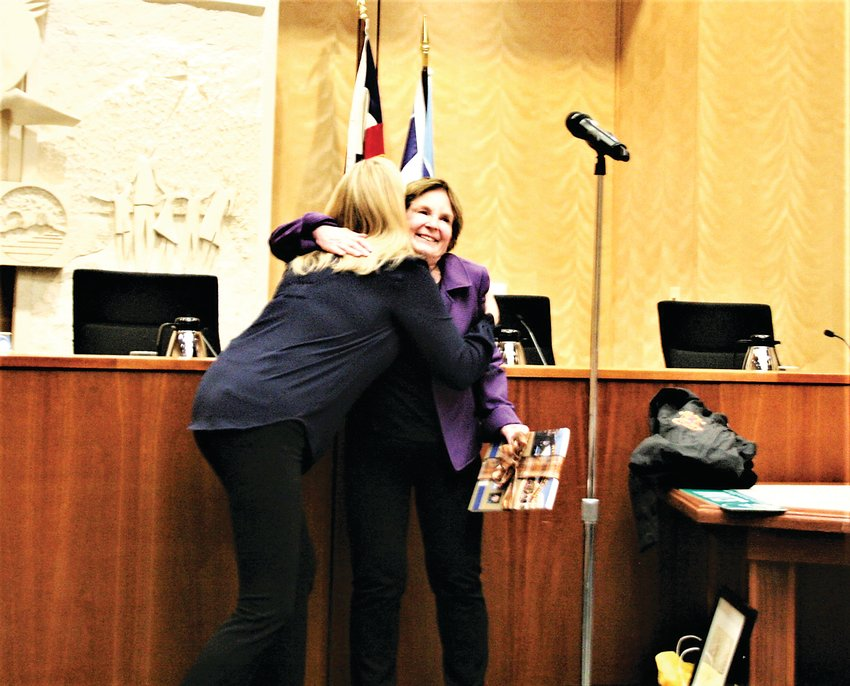 Golden communications manager Karlyn Tilley, left, hugs outgoing Golden mayor Marjorie Sloan, right, after gifting her a copy of the Golden Informer monthly community magazine before the city council meeting on Thursday, Jan. 9.