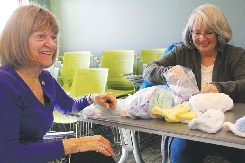 Mary Alice Jackson, 79, left, sits with Karen Fleck as she makes hats for babies. That's an activity that members of the Rotary Club of Centennial regularly take up together. The group did that on the side as others played various games at Koelbel Library.