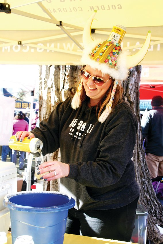 Laura Ukowich pours a Favorite Blonde beer at the Holidaily tent at the UllrGrass Music & Beer Festival last year.