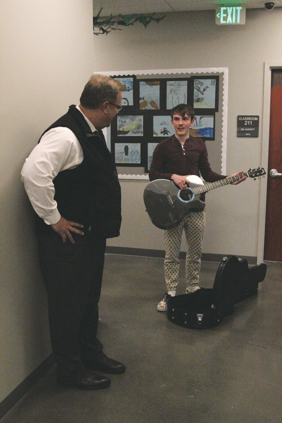 Collin Rogers-Peckham shows his principal Jeff Broeker a guitar he received as an early graduation present.
