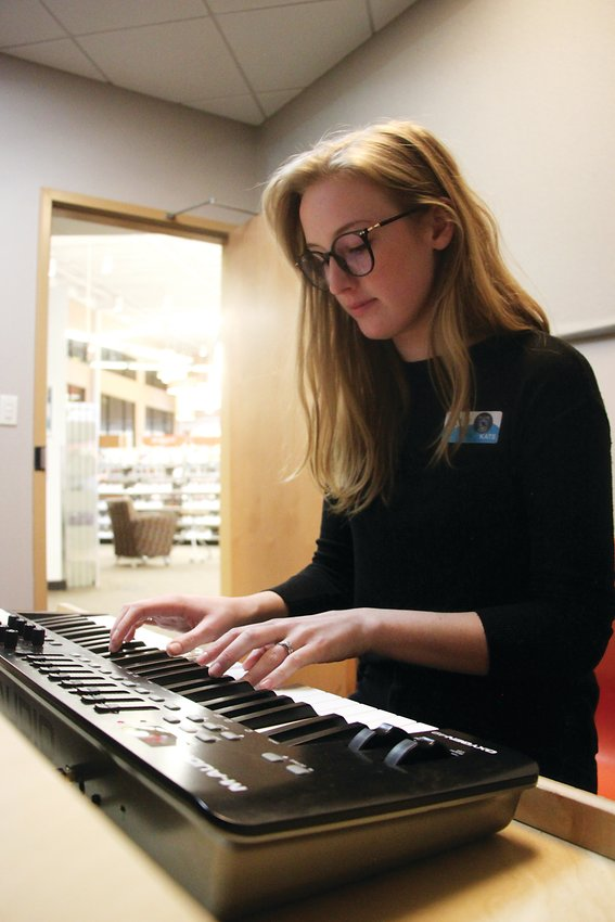Arapahoe Libraries technology specialist Kate O'Brien plays a tune in Southglenn Library's recording studio.