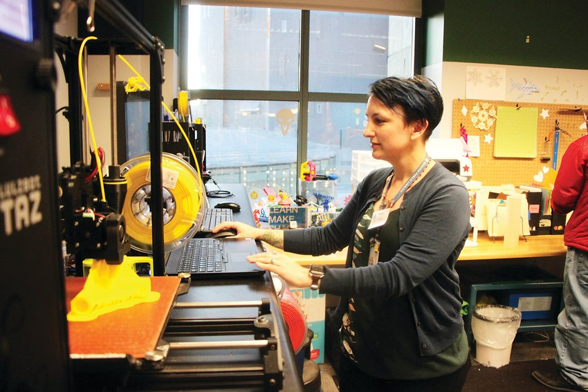 Ashley Kazyaka checks on the progress of a 3D-printed tent pole connector at the Denver Public Library Central Branch's IdeaLAB makerspace. Kazyaka oversees the district's makerspace program, which gives patrons access to a wide variety of tools and machinery.