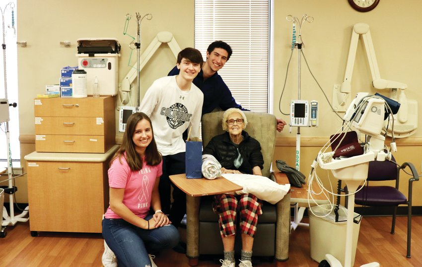 DRHS student Michaela Mossbrucker and Columbine students Garrett Rogers and Luke O'Brien spend time with Arvada resident Jeannene Fullen at the infusion center.