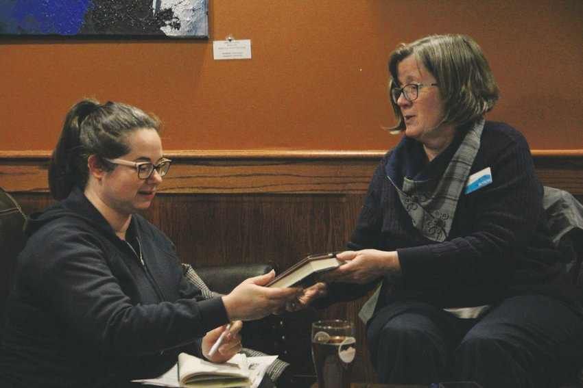 Alyson Corcoran, a librarian with Arapahoe Libraries, hands a book to Allyson Henry, of Centennial, at a Books on Tap event hosted by the library district at a local brewing company.