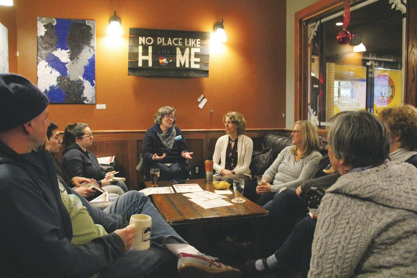 Members of the Books on Tap book club sit at Halfpenny Brewing Company Jan. 22 during a discussion.
