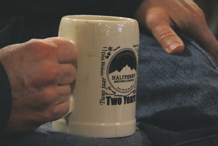 A book club member holds a Halfpenny Brewing Company mug.