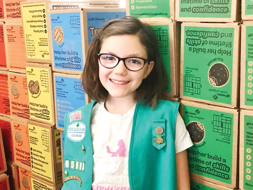 Bianca Morris, 10, stands with a delivery of Girl Scout cookies. She and the other girls in her troop will be spending a third of this year's revenue on a fun day out, saving a third of it for a future troop trip and investing a third of it to go toward their Bronze project, which will benefit the community.