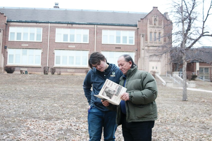 Advocates for re-opening the school as a public school for neighborhood children, Daniel McAllister, left, and his father Ray McAllister, look up some facts about Rosedale Elementary in a history book that Ray McAllister co-authored.