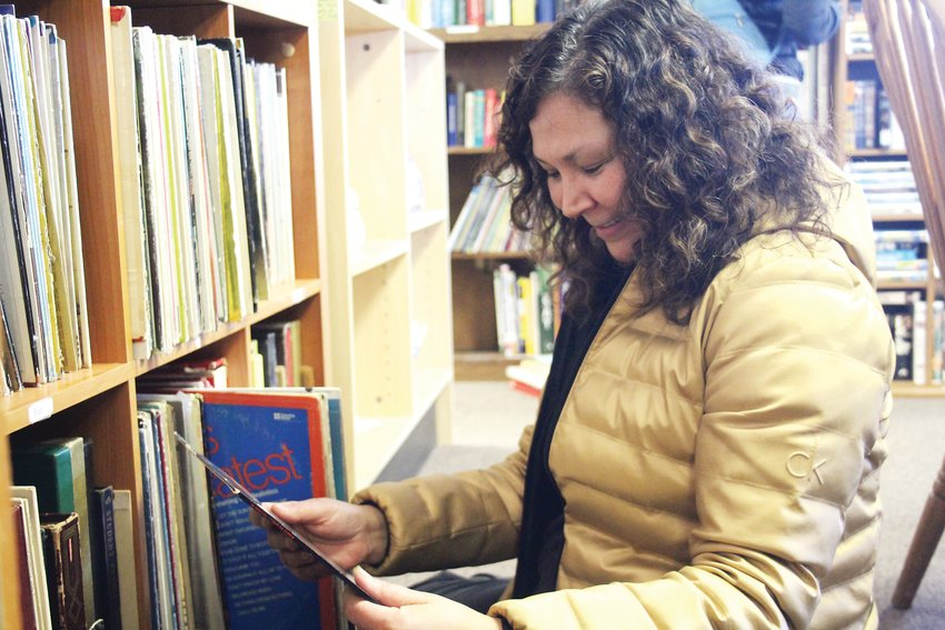 Anna Nicks goes through old records at Global Thrift. The thrift store is operated by volunteers and benefits Global Refuge, an organization that carries out international projects for refugees.