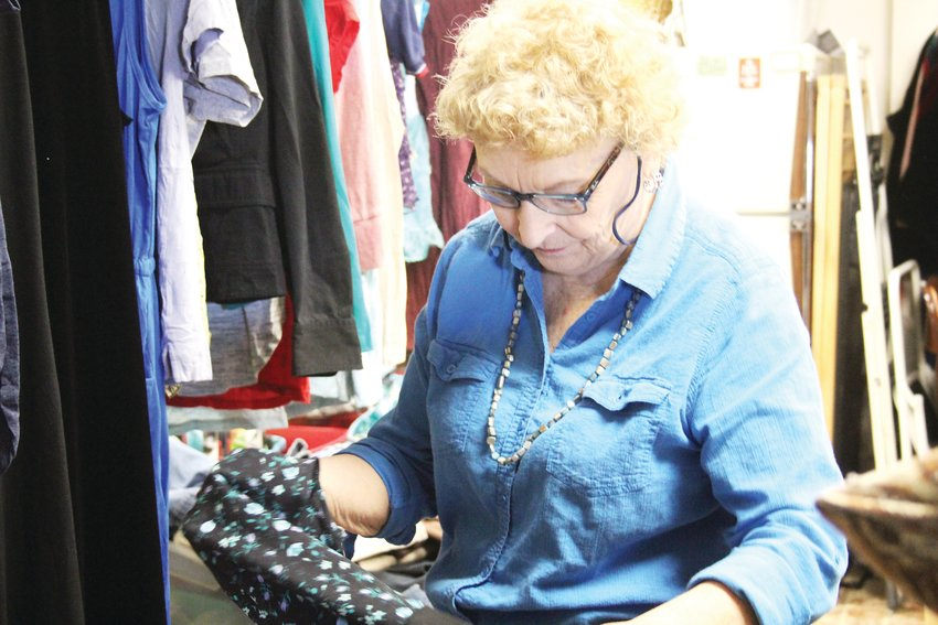 Mary Hooper sorts through clothes at Global Thrift. Shopping at thrift stores can help prevent clothing from going to the land field, according to Elena Karpova, a professor at the University of North Carolina at Greensboro's Department of Consumer, Apparel and Retail Studies.