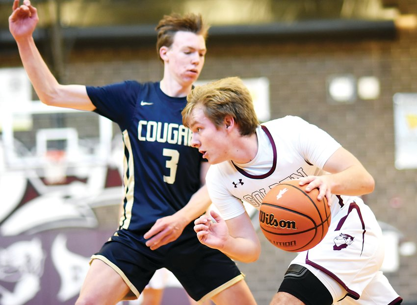 Golden senior Jack Anderson drives baseline on Evergreen senior Cooper Dyess during the Class 4A Jeffco League game Feb. 8. The Demons stayed 1-game ahead of rival Wheat Ridge in the conference standings with a 59-53 victory.