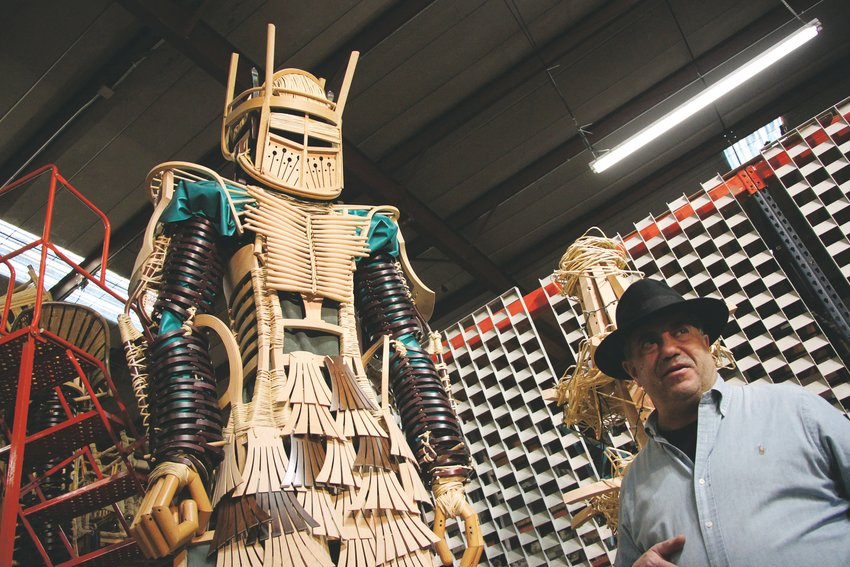 "Steve Farland, owner of the Chairman, stands beside ""The Guardian,"" one of seven towering statues made of chairs."