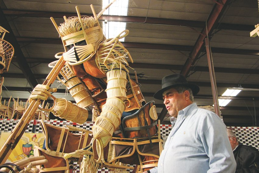 "Steve Farland next to ""The Creator,"" one of seven massive statues made of chairs. Soon to lose his warehouse space, Farland is seeking a home for all seven of his statues."