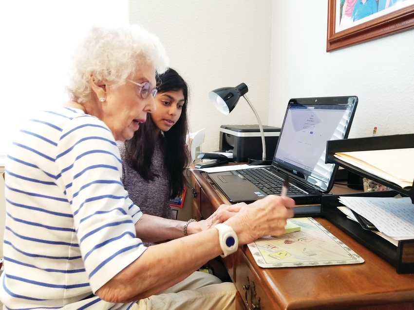 A teen helps an older adult navigate her device. The Generation Tech organization seeks to provide the age 50-plus population with better ability to use technology.