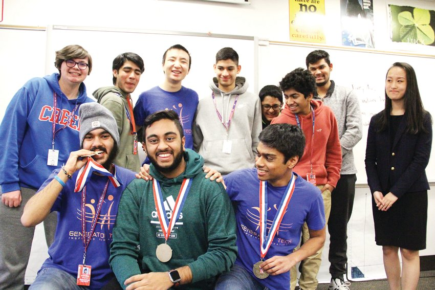 Members at a Generation Tech meeting at Cherry Creek High School laugh Feb. 6 while posing for a photo. Some group members wore medals signifying a large number of volunteer hours they have completed.