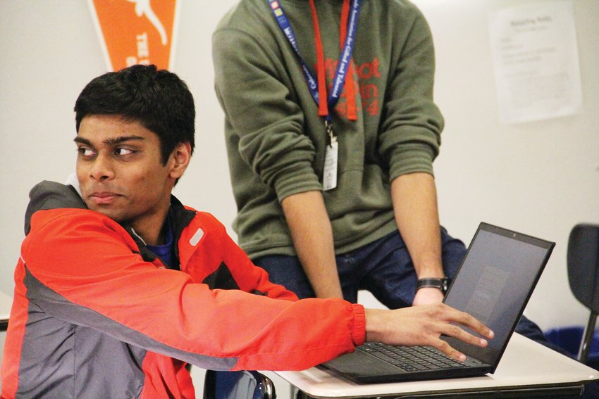 Shrujal Mogadati, a Cherry Creek High School senior, holds back laughter Feb. 6 during a Generation Tech exercise in which pairs of club members practice solving tech issues. The student organization teaches older adults how to navigate technology.