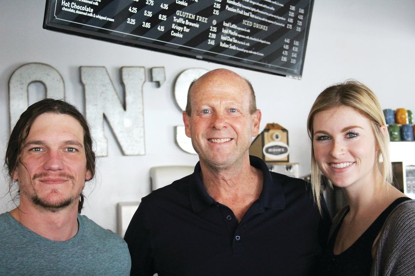 Drew Macalady, left, Brad Nixon and Sarah Bomers pose for a photo at Nixon's Coffee House in Englewood on Feb. 13. Nixon owns the coffee shop and will participate in an 11-month journey of creating a downtown plan for Englewood with others. Macalady and Bomers work at Nixon's Coffee House.
