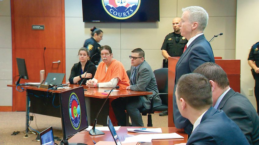 District Attorney George Brauchler addresses the judge during a hearing in the case against James Clanton Feb. 21. Clanton, 62, can be seen in an orange jumpsuit.