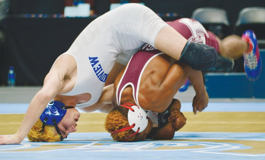 Cherokee Trail's Derek Glenn Jr., right, and Frankie Sanchez of Grandview keep their heads down in the 106-pound Class 5A title match on Feb. 22 at the Pepsi Center. Glenn won the match and captured the first individual state wrestling title for Cherokee Trail.