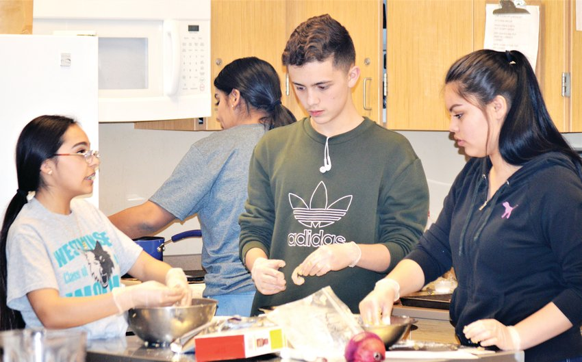 Freshmen Anita Cordova and Siban Jacildo and junior Bianca Martinez coat their shrimp with a mixture of breadcrumbs and crushed Girl Scout Somoas cookies on their way to making a Thai-themed meal that ended up taking second place in a Westminster High School culinary program contest.