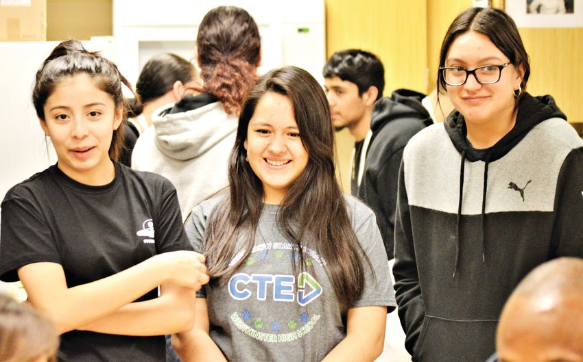 Westminster High School culinary arts students Keila Urena, Cassandra Campos Cruz and Analy Guillen Saucedo watch as the judges sample the chicken satay they made using peanut butter-flavored Girl Scout Tagalong cookies.