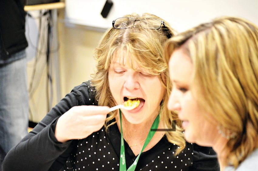 Westminster High School administrative assistant Penny Wesanko samples the mango fried rice that accompanied the fried Thai shrimp made with crushed Girl Scout Samoa cookies, Feb. 19.