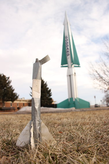 A child's duct-tape rocket sits on the lawn outside Goddard Middle School, backed by the school's historic Nike Hercules missile. The district has decided to get rid of the missile to expand the parking lot, and longtime locals are hoping to find it a new home.