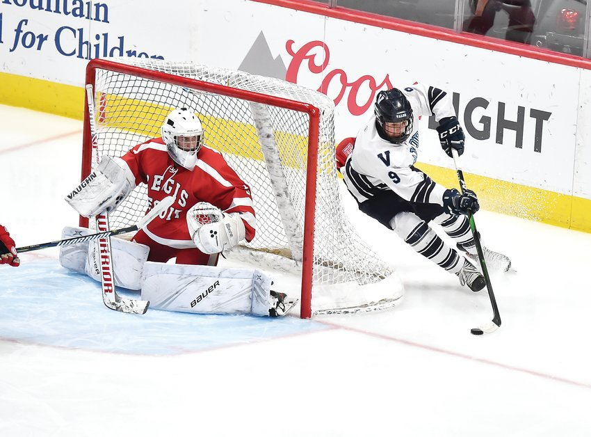 Valor Christian's Evan Pahos (9) emerges from the backside of the goal as Regis Jesuit's Gage Bussey closes off access down low. The Eagles ended up on top 2-1 in Frozen Four action March 5 at the Pepsi Center and advanced to the finals.
