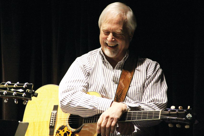 Mike Overn, of Aurora, laughs on stage at Koelbel Library's recurring event for singers and songwriters.