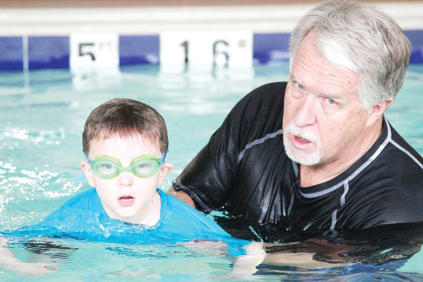 Russ Marsh leads Dean Aizenman, 4, through a swim lesson at Smilefish Swim School in Castle Rock.