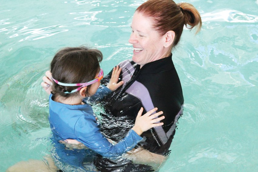 Jennifer Dombrowski helps a student into the pool during an ISR lesson at the Highlands Ranch Recreation Center at Eastridge.