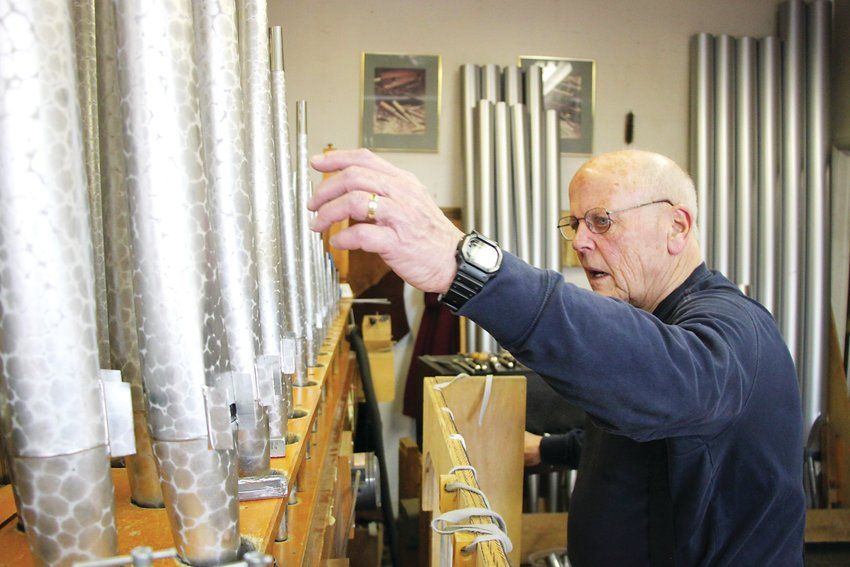 Rick Morel, a third-generation pipe organ builder, checks the tuning on a restoration job from Littleton's St. Mary Catholic Parish. Pipe organs were once staples of American life, but have begun to fade in recent decades, Morel said.