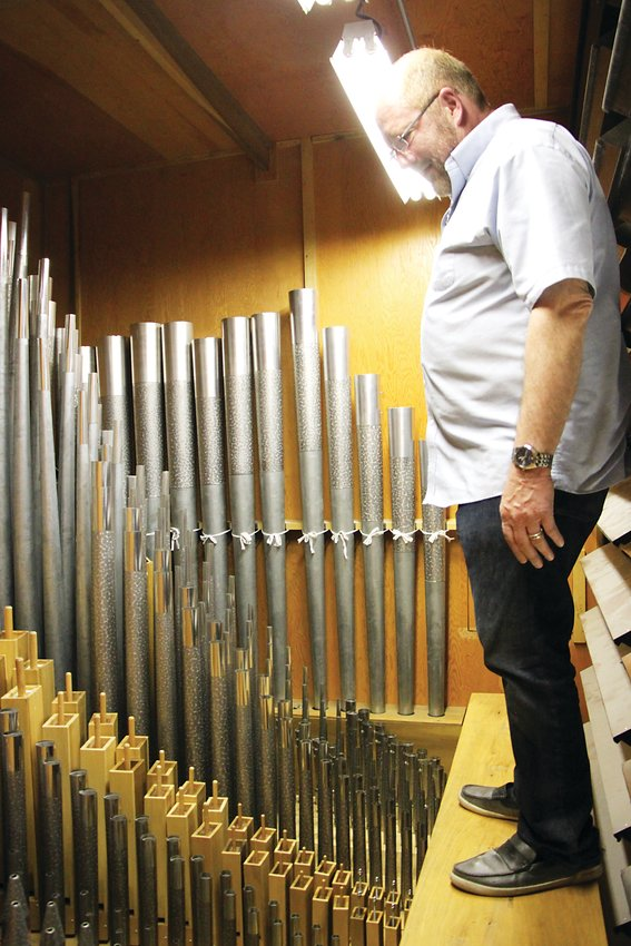 Michael Zehnder, who leads musical worship at Littleton's Ascension Lutheran Church, stands inside the heart of the church's 1950s-vintage neo-baroque style pipe organ.
