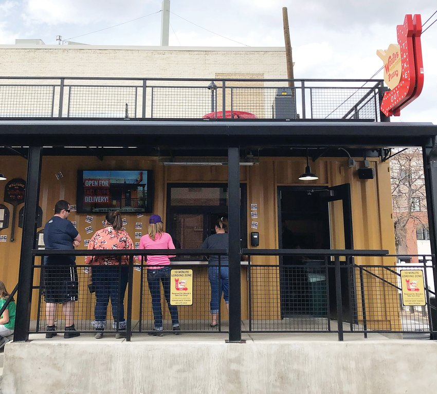 Customers stand at the take-out window at Woody's Wood Fired Pizza.