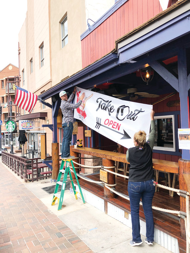 Woody's Wood Fired Pizza owner John Bortles and a manager hang up a sign announcing the availability of take-out at the restaurant on March 18.