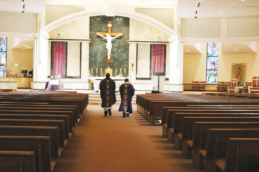 Father John Judanha and Deacon George Morin walk down the aisle at St. Thomas More Catholic Church in Centennial before beginning their livestreamed service. The church was nearly empty except for a few staff members and the church's AV team.