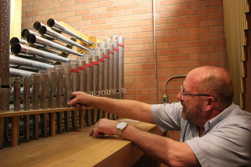 Michael Zehnder inspects some of the smaller pipes inside Ascension Lutheran Church's pipe organ.