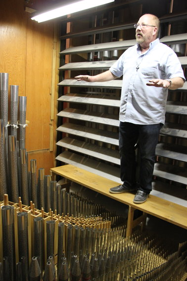 Michael Zehnder stands inside Ascension Lutheran Church's pipe organ.