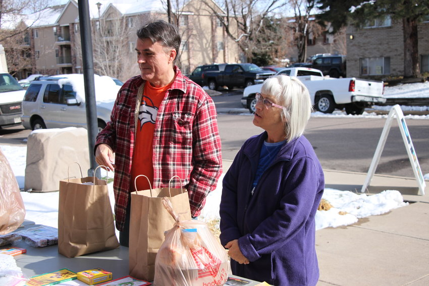 Leigh Dehne, left, and Linda Summers stop by Break Bread in Littleton to pick up a free meal on March 21. Both said they spend all week looking forward to the companionship they enjoy at the free weekly dinner, but for now take-out will have to do.
