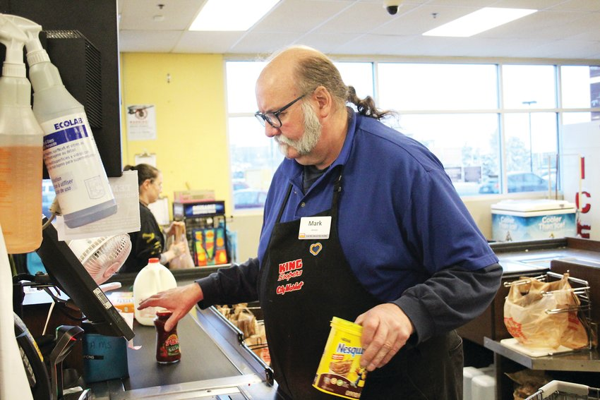 Mark Meek, a King Soopers checker, checks out chocolate milk mix. King Soopers has recently modified its hours to be open from 7 a.m. to 8 p.m. as the COVID-19 pandemic has caused grocery stores to be consistently busy in many parts of the state.