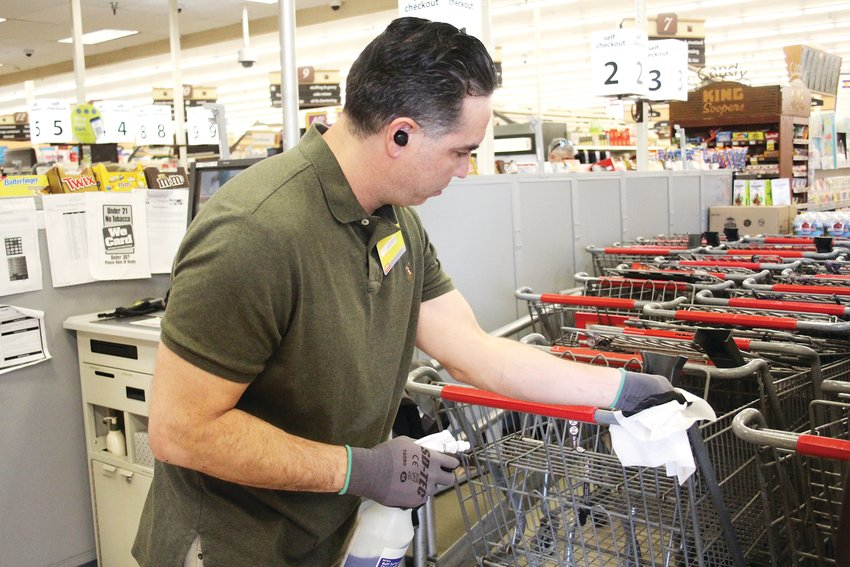 Andrew Vigil disinfects grocery carts at the King Soopers at 6350 Sheridan Blvd. Vigil isn't an employee for the grocery store. Instead, he has been finding work through People Ready, an industrial staffing agency. King Soopers has offered temporary work through People Ready.