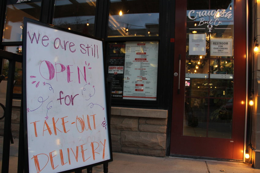 "A sign outside Crawfish Boil Co. restaurant and bar reads, ""We are still open for take-out and delivery."" Most businesses at The Streets at SouthGlenn are closed amid the spread of COVID-19, but many restaurants there are selling food for off-premises consumption, as they are across the state."