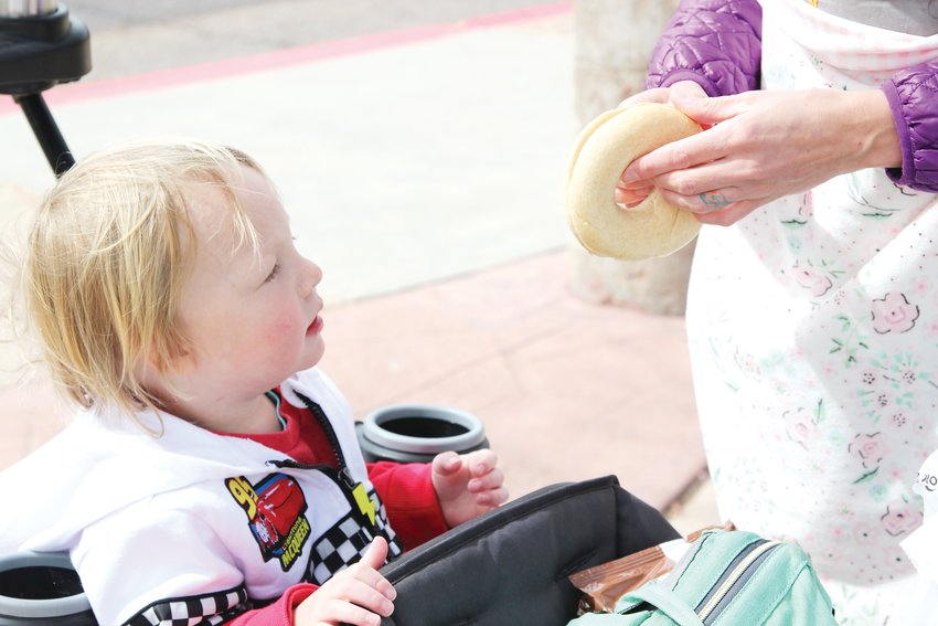 Kristen Sortman prepares a bagel for 3-year-old Flynn from the sack lunch they picked up a South Ridge Elementary School on March 23.
