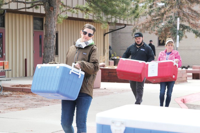 Jen Peifer, manager of operations for Nutrition Services at the Douglas County School District, unloads coolers packed with lunches for children on March 23.