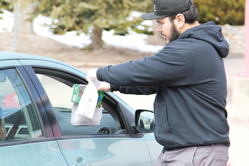 Families picking up lunches from South Ridge Elementary School on March 23 were served in a drive-through manner, as staff handed them the number of meals requested without them needing to get out of their vehicles.